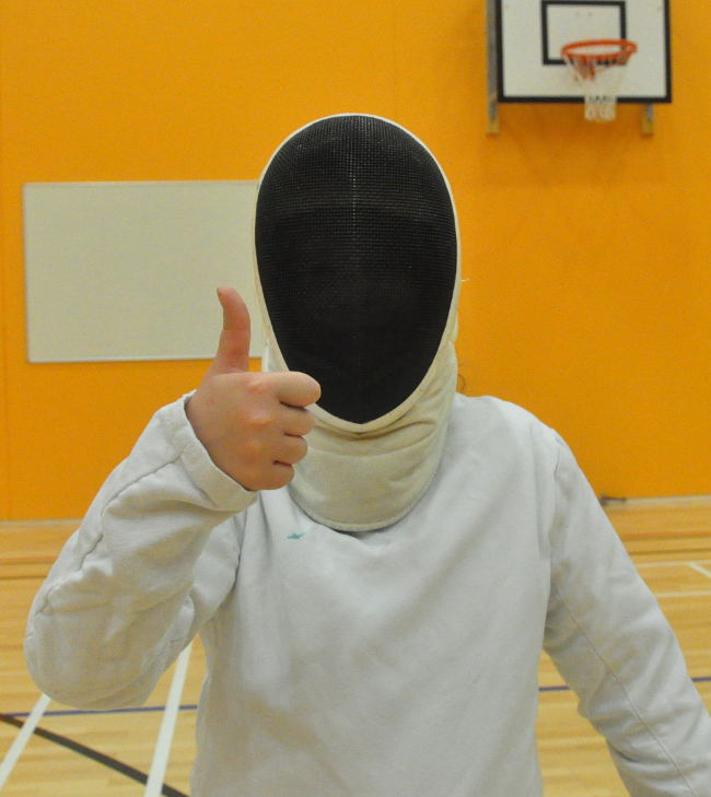 Picture of a young fencer waring a mask and giving thumbs-up